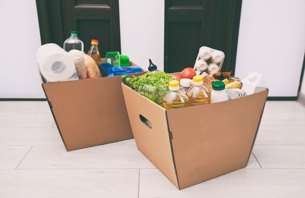 ドアの近くの自宅の床に食料品店からの製品が入った完全な段ボールのエコボックス Premium写真