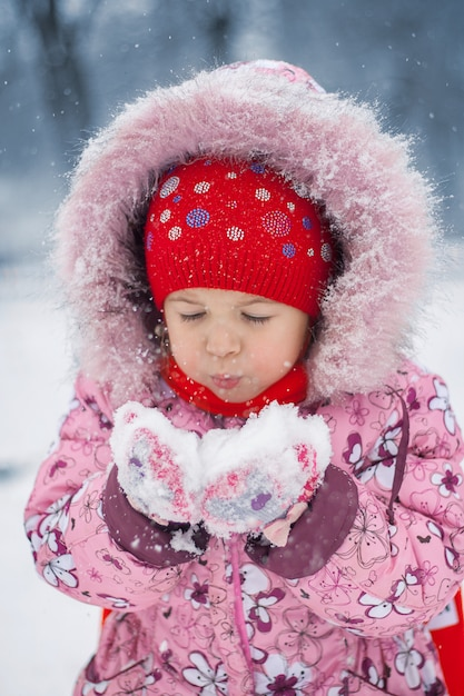 The girl blows on snow in hands Premium Photo