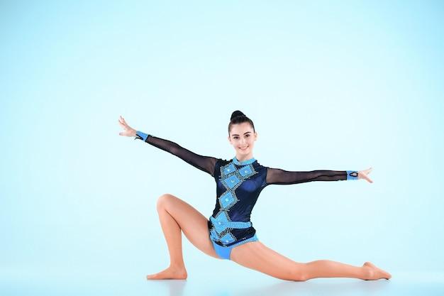 Девушка занимается гимнастикой на голубом пространстве Бесплатные Фотографии