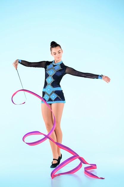 Девушка делает гимнастику танец с цветной лентой на синем пространстве Бесплатные Фотографии