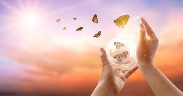 少女は瓶から蝶を解放し、黄金の青い瞬間自由の概念 Premium写真