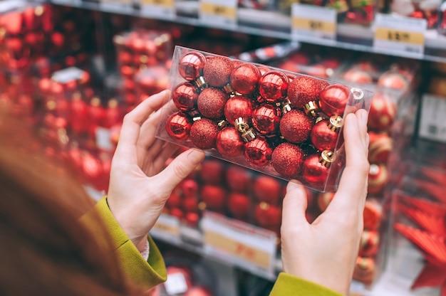 소녀는 크리스마스와 새해를 장식하기 위해 손에 장식용 빨간 공을 들고 있습니다. 프리미엄 사진