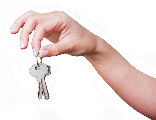女の子は白い背景と分離彼女の手でキーを保持します Premium写真