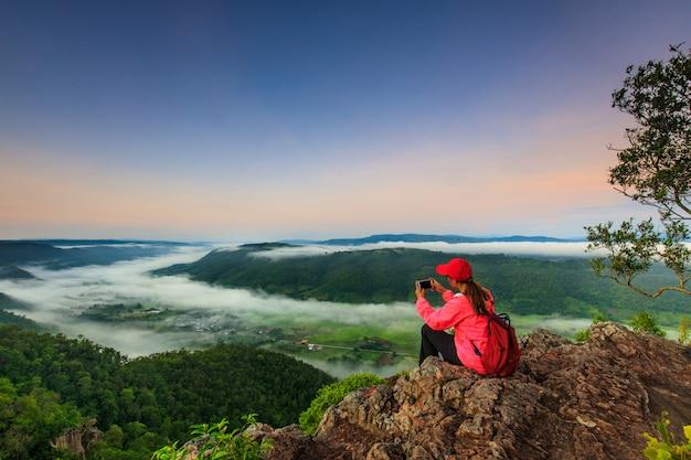 Девушка в красной куртке стоит на горе Premium Фотографии