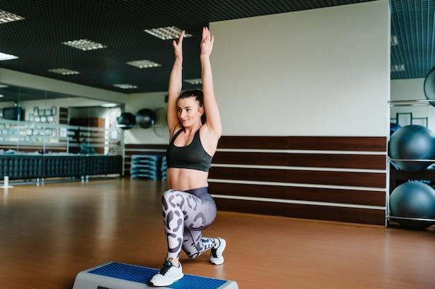 スポーツシューズの女の子がステッププラットフォームに足を踏み入れ、ジムでエクササイズ、エアロビクスを行います Premium写真