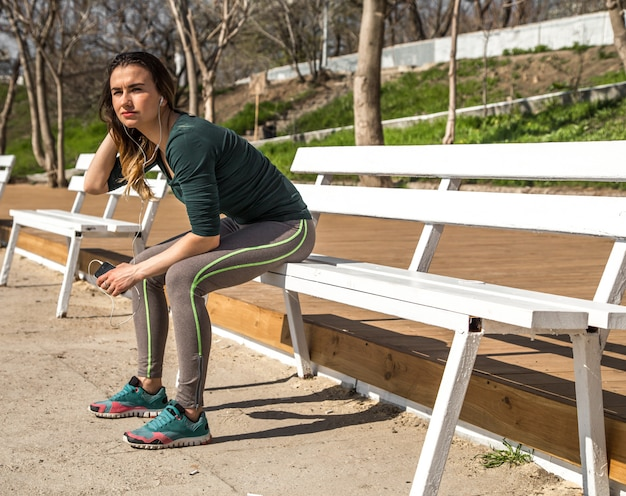 音楽を聴くベンチでスポーツウェアの少女 無料写真