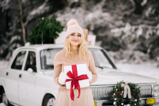 女の子はクリスマスの準備をしていて、レトロな車の背景に彼女の手に贈り物を持って立っています。レトロな車の屋根は、クリスマスツリー、贈り物、冬の雪に覆われた森の中の花輪です。 Premium写真