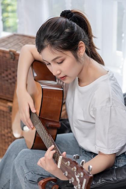 女の子は椅子に座ってギターを弾いています。 無料写真