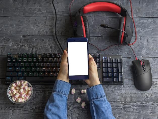 Девушка держит телефон на фоне рабочего стола с игровой клавиатурой, гарнитурой и мышью Premium Фотографии