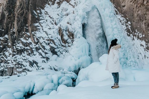 女の子は滝を見ます。冬の滝を背景にした旅行者。 Premium写真
