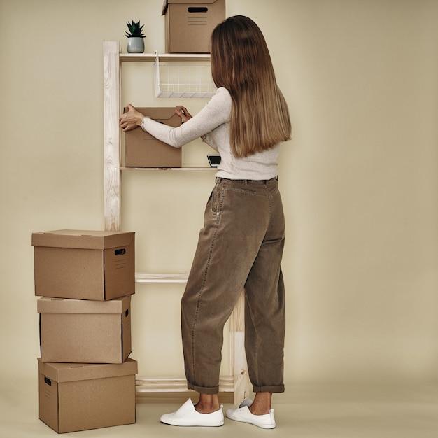 Девушка составляет бумажные коробки на деревянной стойке. экологичное хранение и упаковка. Premium Фотографии