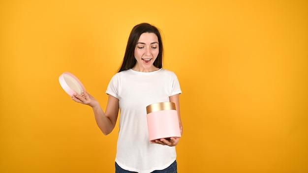 Девушка открывает подарочную коробку Premium Фотографии
