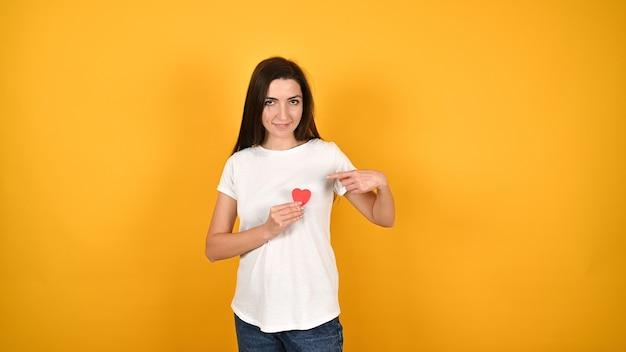 Девушка приложила сердце к груди Premium Фотографии