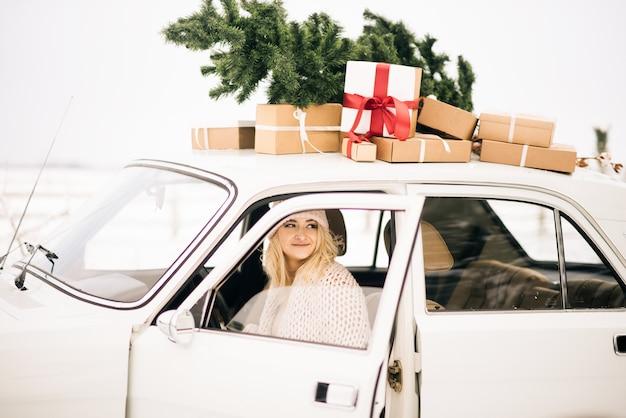 女の子は、クリスマスツリーで飾られたレトロな車に乗って、雪に覆われた森にプレゼントします。冬のクリスマス写真撮影のコンセプト Premium写真