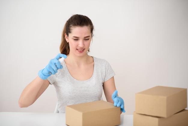 女の子はテーブルのゴム手袋に座って、段ボール箱に消毒剤を吐きます。安全な配達のコンセプト。ウイルスとの戦い Premium写真