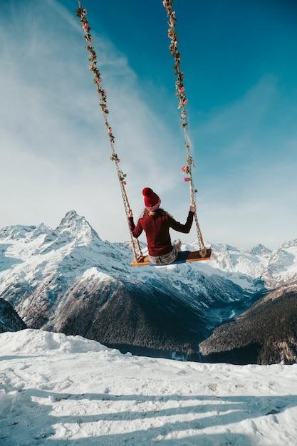 소녀는 뒤에서 산에서 그네에 앉는다. 심연 위로 하늘의 스윙. 프리미엄 사진