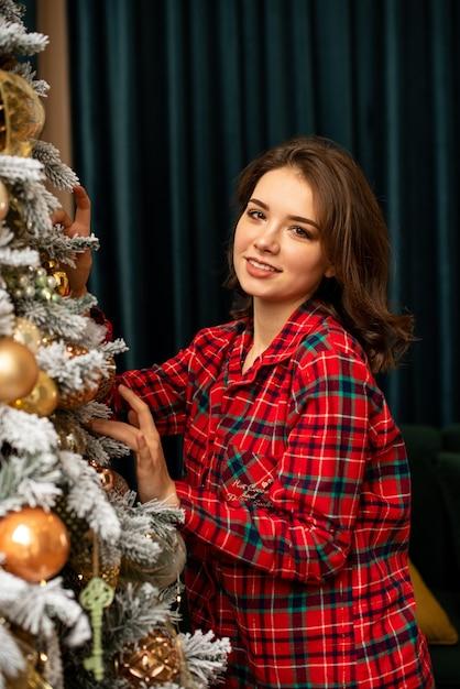 女の子はクリスマスツリーの近くに立って、それを飾ります。彼女は微笑んで、休暇のために家を準備します Premium写真