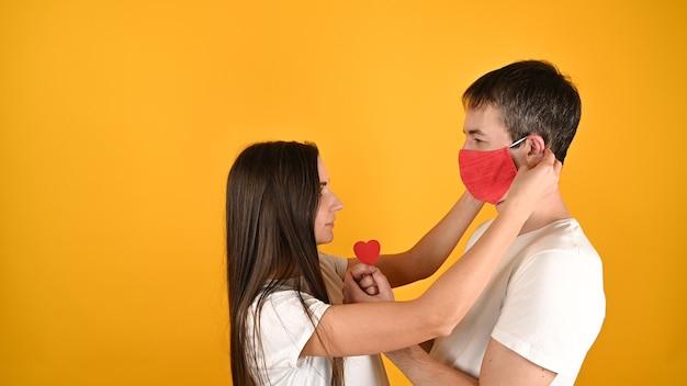 Девушка снимает с парня маску на желтом Premium Фотографии