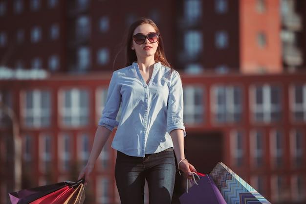 Девушка гуляет с сумками по улицам города в солнечный день Бесплатные Фотографии