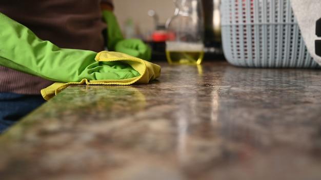 Девушка моет столешницу на кухне. Premium Фотографии
