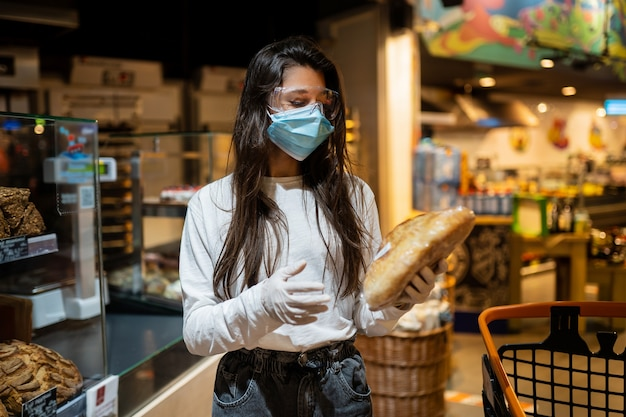 Девушка в хирургической маске собирается покупать хлеб. Бесплатные Фотографии