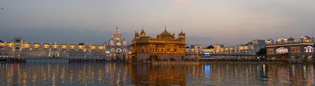 インドのパンジャブ州アムリトサルにある黄金寺院は、シーク教の宗教の中で最も神聖な象徴であり、崇拝の場所です。夜に照らされ、湖に反映されます。 Premium写真