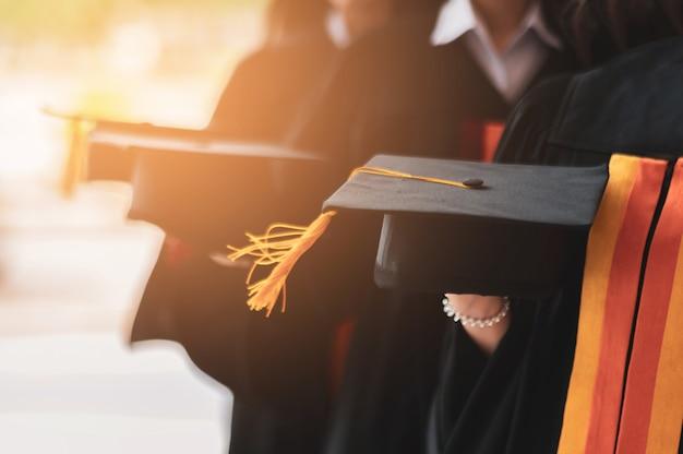 卒業生グループは大学の卒業式で黒い帽子、黒い帽子をかぶった。 Premium写真