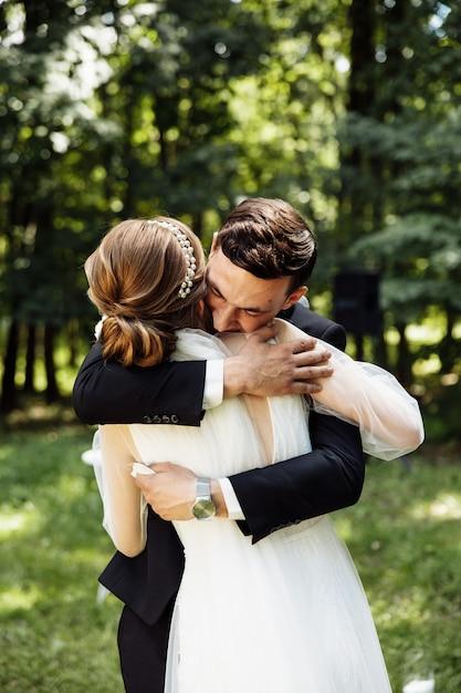 신랑과 신부는 결혼식에서 서로에게 약속을 읽었습니다. 신혼 부부는 반지를 교환합니다. 아치에 의해 신부와 신랑. 프리미엄 사진