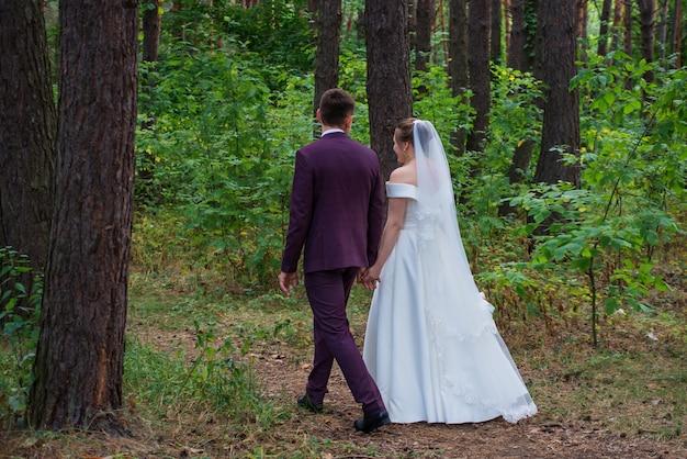 Жених и невеста гуляют по лесу в свадебных платьях Premium Фотографии