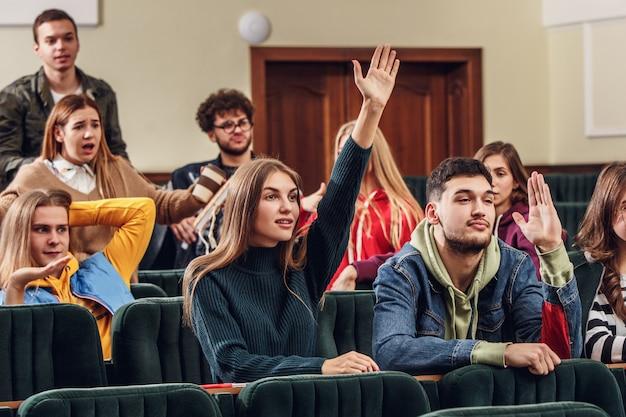 Группа веселых счастливых студентов, сидящих в лекционном зале перед уроком Бесплатные Фотографии