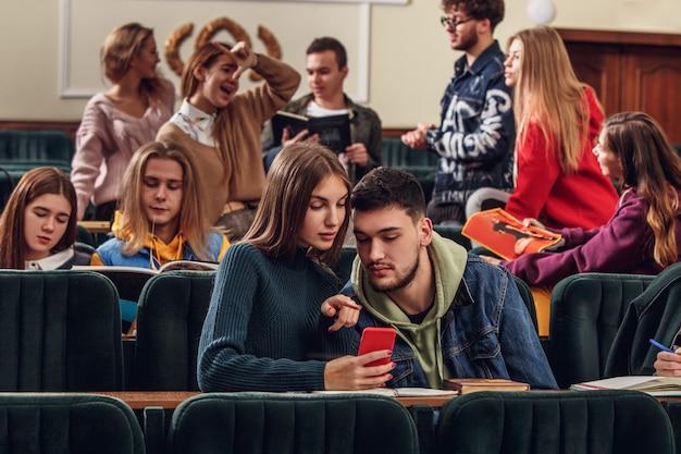 レッスン前に講堂に座っている陽気な幸せな学生のグループ 無料写真