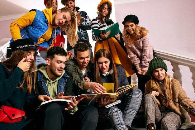 授業前に講堂に座っている陽気な学生のグループ。 無料写真