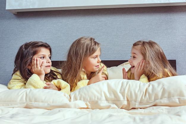 ベッドでググの時間を取っているガールフレンドのグループ 無料写真