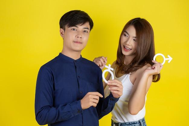 Парень и девушка держат мужской и женский символ на желтой стене Бесплатные Фотографии