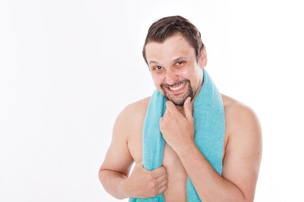 男はひげをなでます。バスルームでの朝のトリートメント。彼女の首に青いタオル。白い背景で隔離されました。コピースペース Premium写真