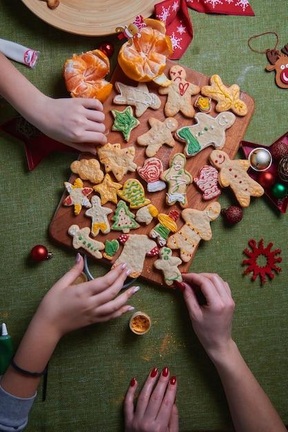 구운 된 생강 남자를 들고 아름 다운 젊은 여자의 손. 집안의 만찬, 가족 저녁 식사의 개념. 새해 전통 개념과 요리 과정. 가족 만들기 프리미엄 사진