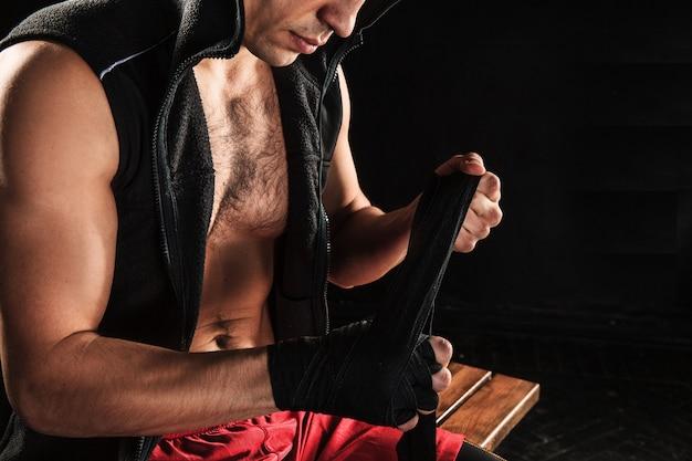 Руки с повязкой мускулистого мужчины, тренирующего кикбоксинг на черном Бесплатные Фотографии