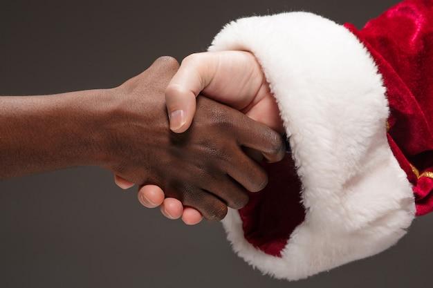 サンタクロースの握手とアフリカ人の手。メリークリスマスのコンセプト 無料写真