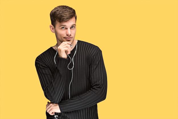 Красивый молодой человек стоит и слушает музыку. привлекательный мужчина держит наушники и мобильный телефон на желтом фоне Бесплатные Фотографии