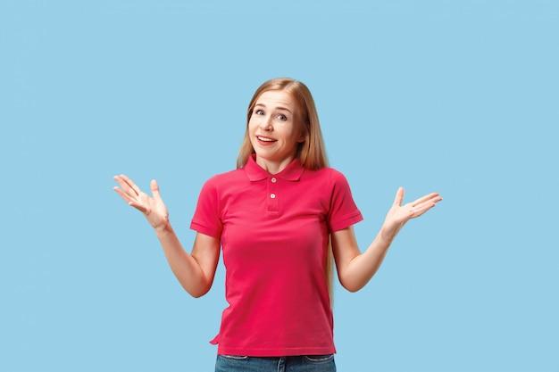 Счастливая бизнес-леди стоя и усмехаясь против голубой стены Бесплатные Фотографии
