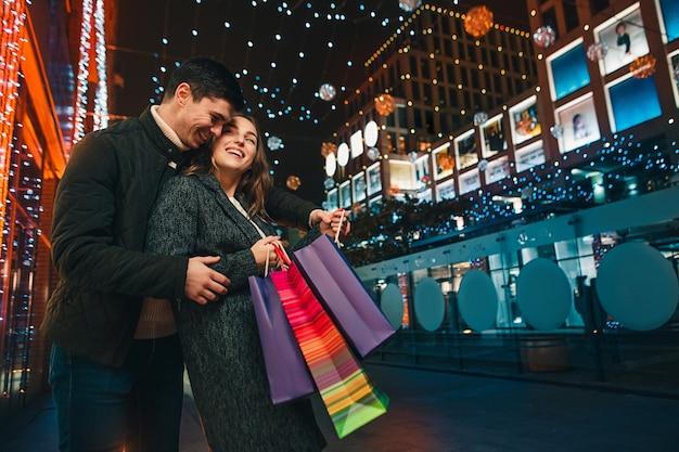 Счастливая пара с хозяйственными сумками, наслаждаясь ночью в городе Бесплатные Фотографии