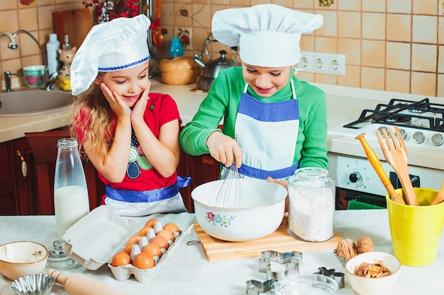 Счастливые двое веселых детишек готовят тесто, пекут печенье на кухне Бесплатные Фотографии