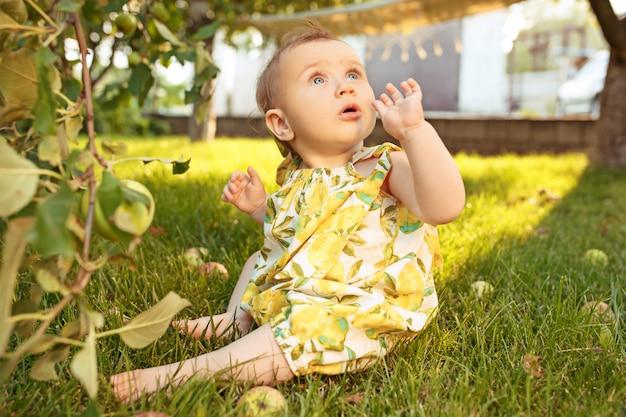 屋外の庭でリンゴを摘みながら幸せな若い女の赤ちゃん 無料写真