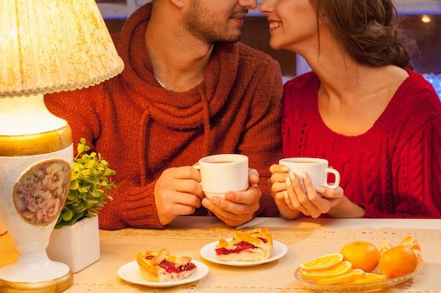 Счастливая молодая пара с чашками чая и пирожными. Бесплатные Фотографии