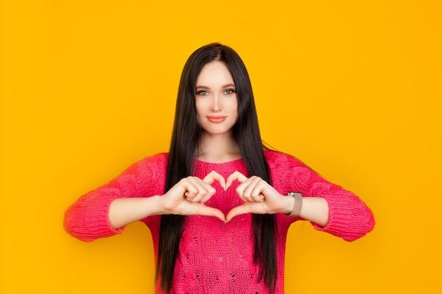 ハートは、ピンクのセーターを着た、明るい黄色の壁の女の子が作った手でできています。コンセプトは愛、愛を与える、信頼と共感の感情で作られています Premium写真