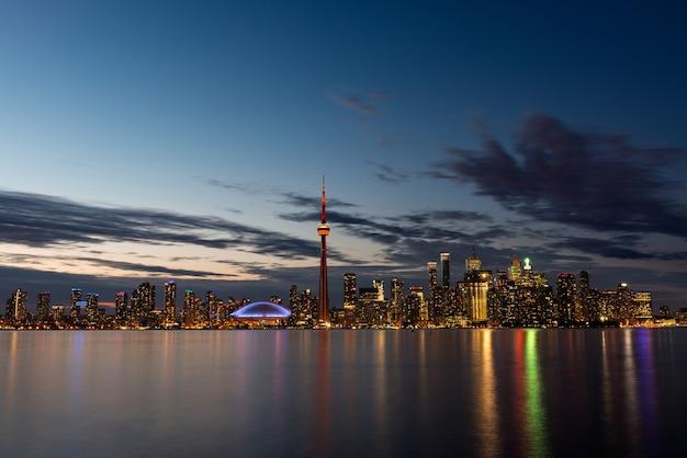 Освещенный горизонт торонто с озером онтарио на переднем плане, вид с центрального острова. Premium Фотографии