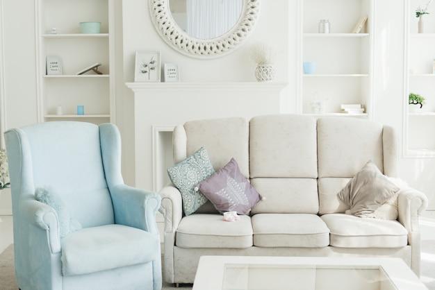 白いソファ、青い肘掛け椅子、背面の本棚を備えたモダンなリビングルームのインテリア Premium写真