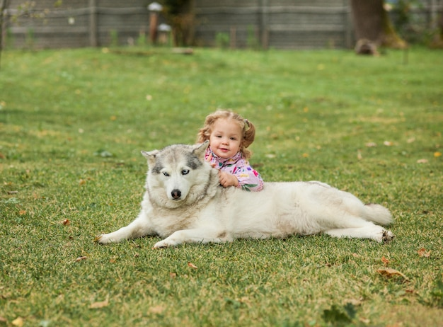 Маленькая девочка, играя с собакой против зеленой травы в парке Бесплатные Фотографии