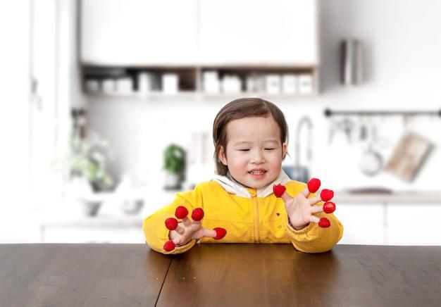 Маленькая девочка играла с малиной на пальцах Premium Фотографии