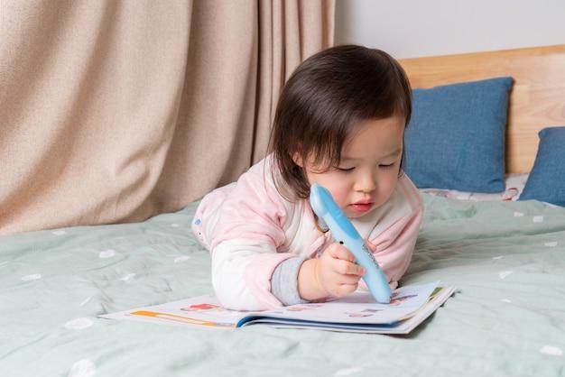 어린 소녀는 침대에서 책을 읽고있었습니다 프리미엄 사진